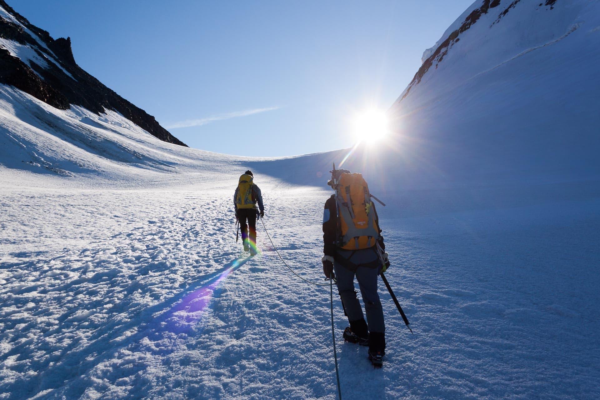 Alpenfotogtrafie: Es ist sehr früh am Morgen, kalt und klar. Der Schnee knirscht unter den Steigeisen und quietscht unter dem Eispickel. Dann, nach einiger Zeit, der erste Sonnenstrahl -ein Geschenk.