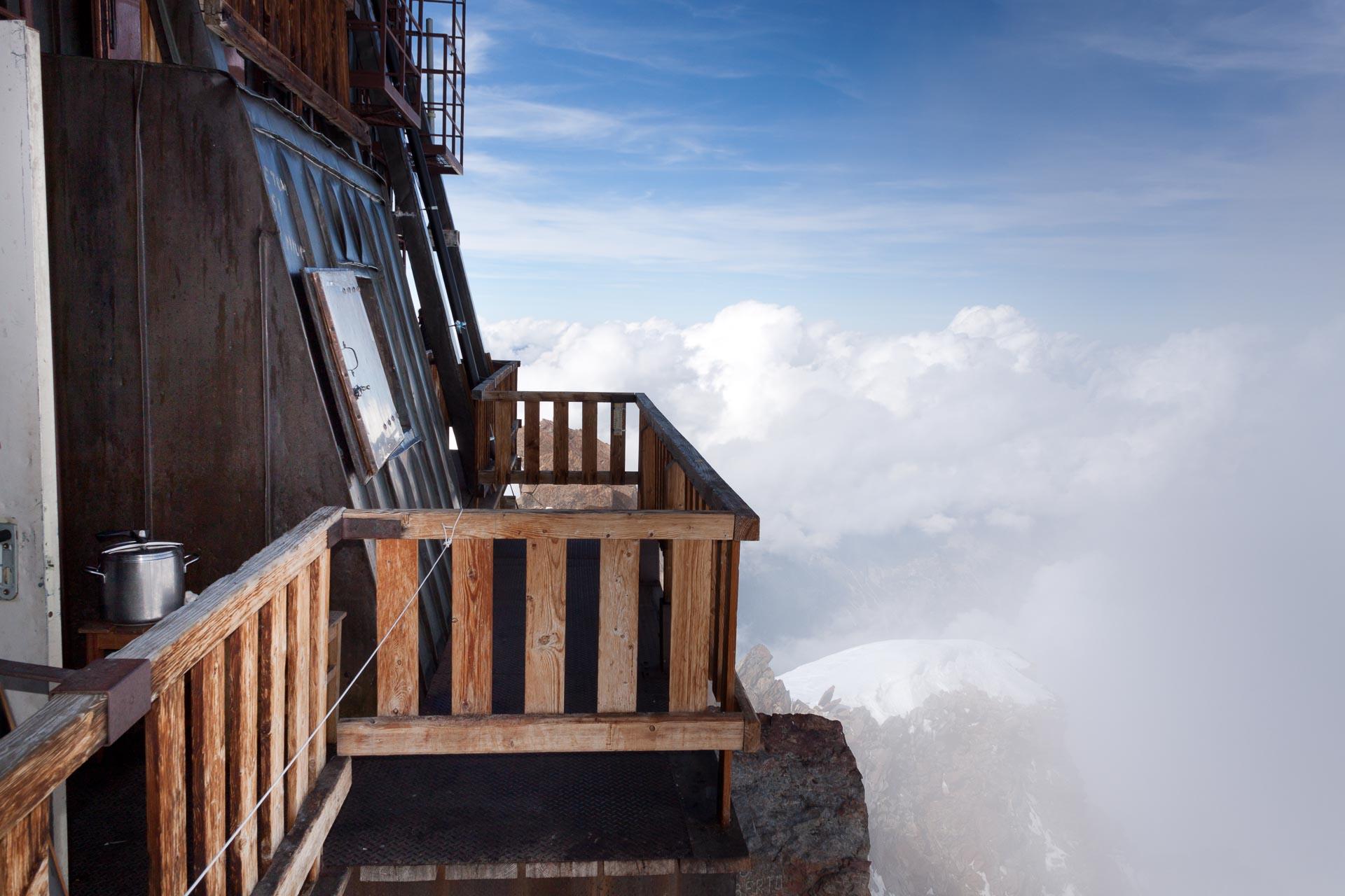 Balkon der Capanna Margherita mit viel Luft drunter. Der Holzbau ist mit einem Kupfermantel versehen. Dadurch wird die Hütte nach dem Prinzip des Faradayschen Käfigs gegen elektrische Felder, wie sie bei Blitzeinschlägen vorkommen, abgeschirmt.